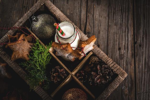 Dolci e dolcetti di natale, bottiglia con latte per babbo natale con biscotti di panpepato stelle con corda di decorazione e decorazioni natalizie, in scatola di legno, legno vecchio, vista dall'alto
