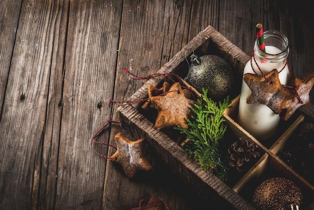 Dolci e dolcetti di natale, bottiglia con latte per babbo natale con biscotti di panpepato stelle con corda di decorazione e decorazioni natalizie, in scatola di legno, legno vecchio,
