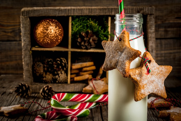 Dolci e dolcetti di natale, bottiglie con latte per babbo natale con biscotti di panpepato con decorazioni di corda e decorazioni natalizie, legno vecchio,