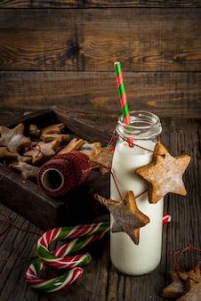 Dolci e dolcetti di natale, bottiglie con latte per babbo natale con biscotti di panpepato stelle con corda di decorazione, legno vecchio,