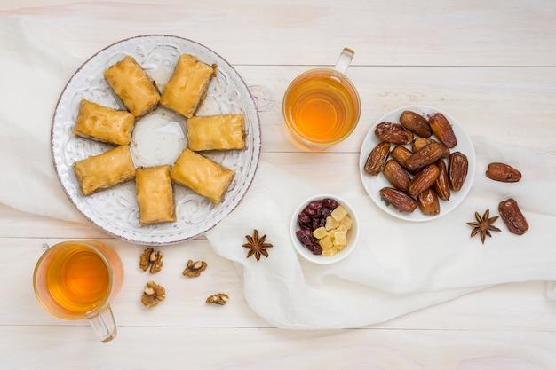 Dolci orientali con frutta data e tazze da tè