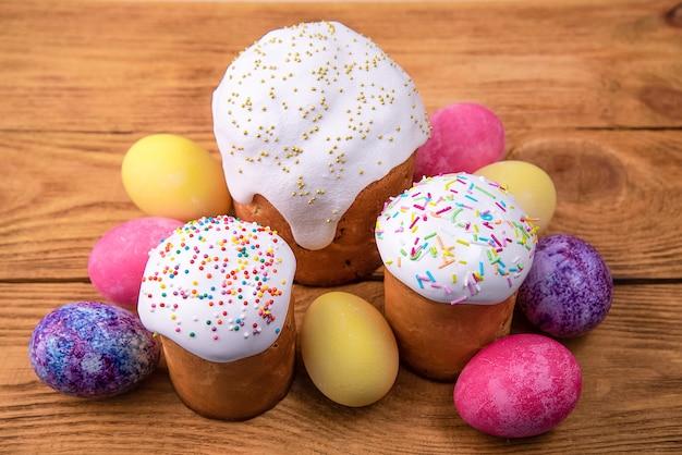 Dolci pasquali e uova colorate di pasqua su uno sfondo di legno. festa religiosa di pasqua luminosa.