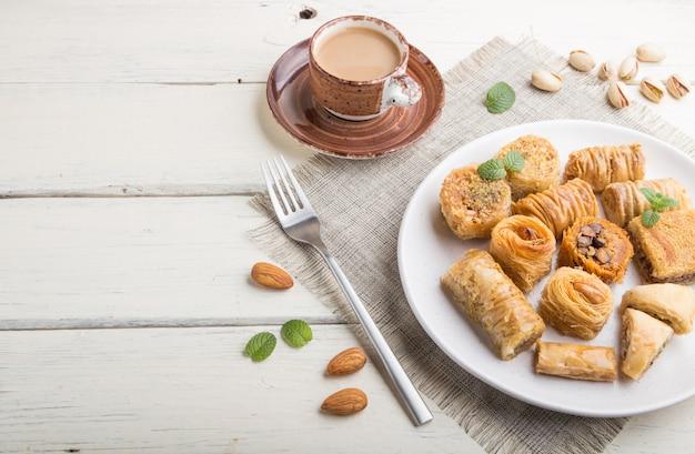 Dolci tradizionali arabi (kunafa, baklava) e una tazza di caffè su una superficie di legno bianca. vista laterale, copia spazio.