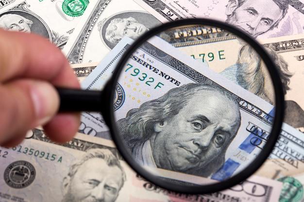 Dollari americani in uno sfondo di lente di ingrandimento