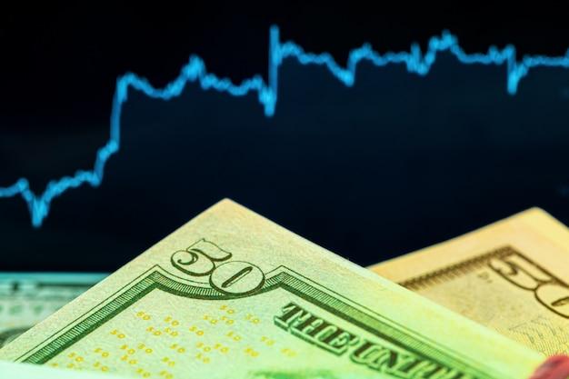 Dollari di fronte a un monitor con un grafico dei prezzi. forex e trading. avvicinamento.