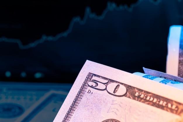Dollari di fronte a un monitor con un grafico dei prezzi