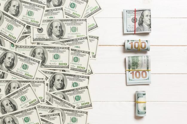 Dollari di valuta sulla vista superiore del fondo colorato, con il posto vuoto per il vostro concetto dei soldi di affari del testo. cento banconote in dollari con la pila di contanti
