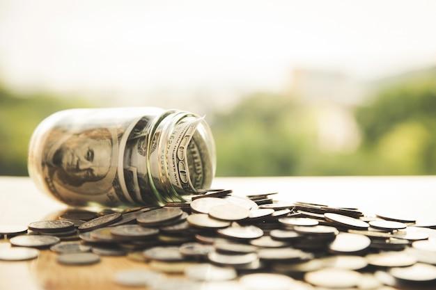 Dollari in un vaso di vetro sulle monete. salvare