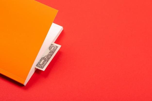 Dollaro come segnalibro nel libro arancione isolato su rosso
