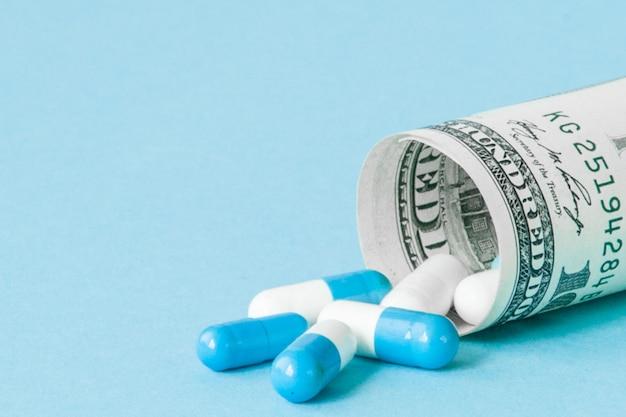 Dollaro dei soldi acciambellato con le pillole che scorrono isolato su fondo blu