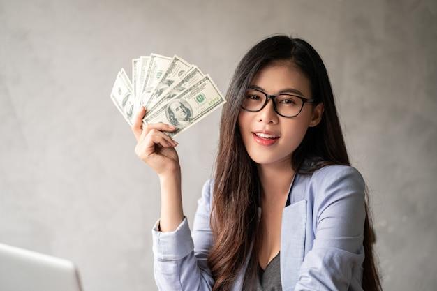 Dollaro in una mano imprenditrice. una donna asiatica lavora da casa o dall'ufficio ed è felice di ricevere denaro in dollari dal lavoro e da una carriera supplementare o un lavoro autonomo a tempo parziale.