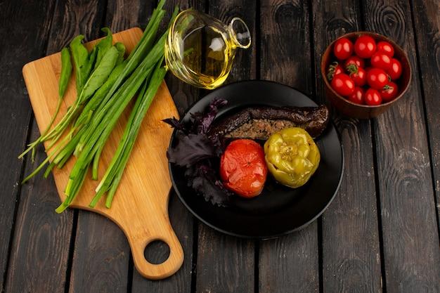 Dolma dolma di verdure con carne macinata all'interno con olio d'oliva verde e pomodori rossi sulla scrivania in legno rustico