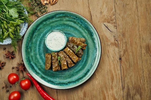 Dolma georgiano tradizionale - riso con carne tritata in foglie di vite su un piatto blu con salsa di yogurt. superficie di legno. vista dall'alto. sarma