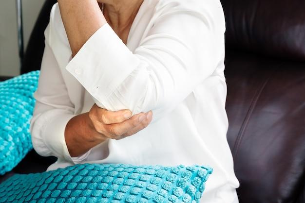 Dolore al gomito / infortunio, vecchia donna che soffre di dolore al gomito, concetto di problema di salute