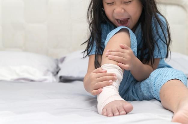 Dolore al piede. ragazzino con una gamba rotta sul letto, bambino dopo l'incidente