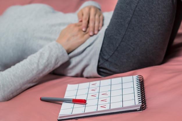 Dolore all'addome durante il periodo. una donna tiene il suo stomaco