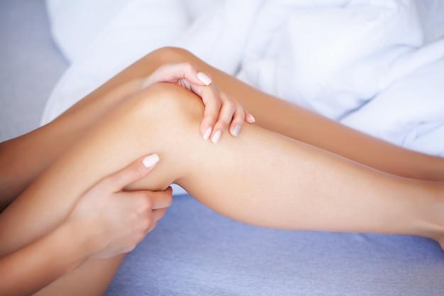Dolore alla gamba o muscolo del polpaccio in una ragazza sul letto, concetto sano