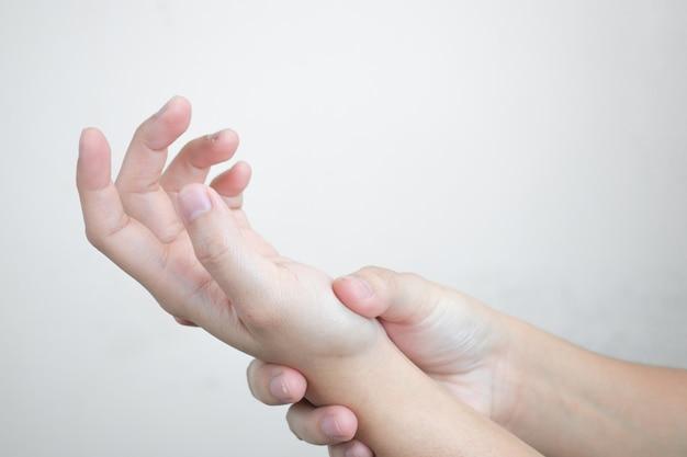 Dolore alle mani. le donne che soffrono di dolore alla mano sul. isolato .