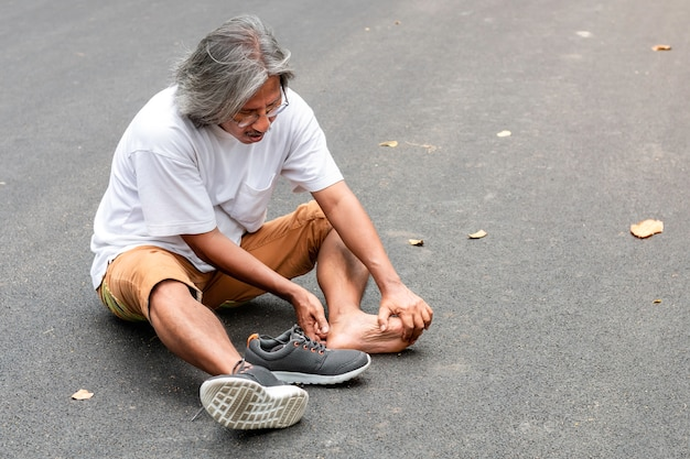 Dolore asiatico della gamba dell'uomo senior durante il pareggiare al parco.
