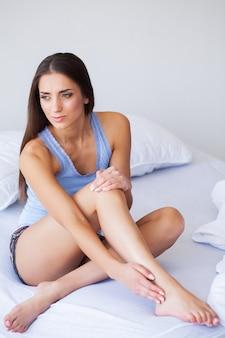 Dolore fisico. bella donna con dolore al ginocchio, sensazione di dolore alle gambe