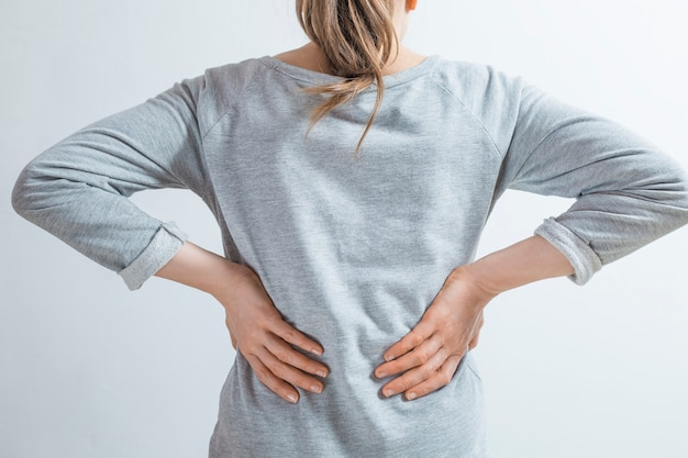 Dolore nei reni. le donne si tengono le mani dietro la schiena.
