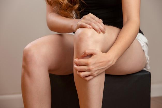 Dolore osseo o ginocchia attorno al ginocchio. la mano della ragazza tiene l'area del ginocchio. donna rossa.