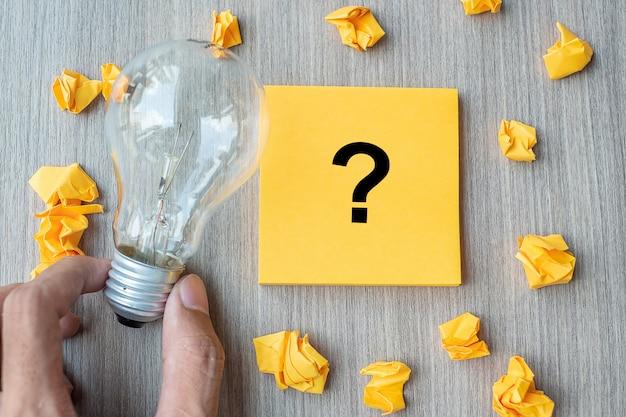 Domande mark (?) parola su nota gialla e carta sbriciolata