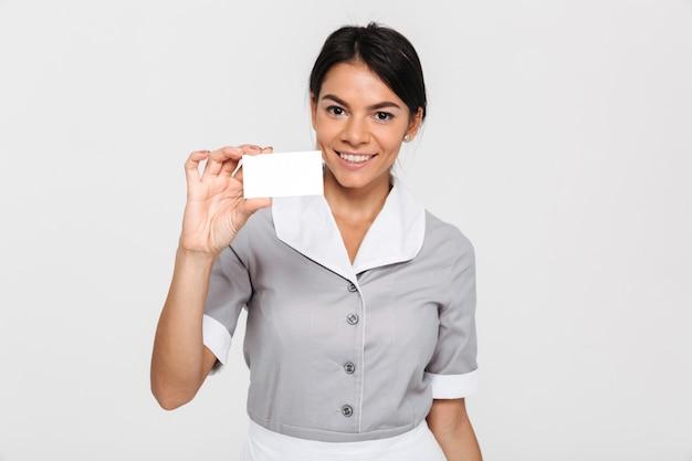 Domestica castana allegra in uniforme che mostra la carta vuota del segno