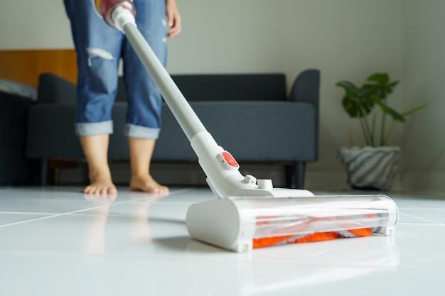 Domestica che pulisce la casa, pulisce il pavimento, aspira usando un aspirapolvere portatile. elimina i germi