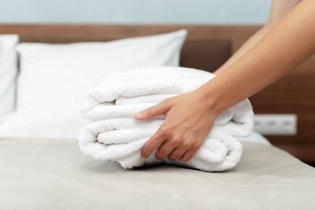 Domestica con asciugamani puliti freschi durante le pulizie in una stanza d'albergo