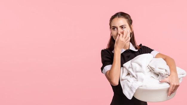 Domestica del colpo medio che tiene un cestino di lavanderia puzzolente