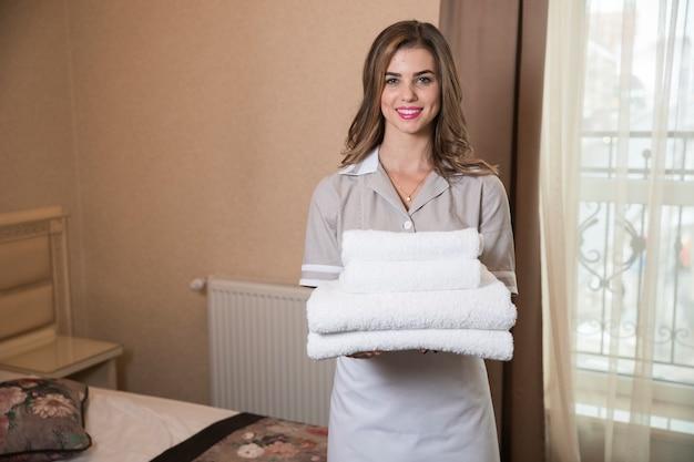 Domestica di servizio della stanza che tiene la pila di asciugamani di bagno bianchi freschi nella camera di albergo