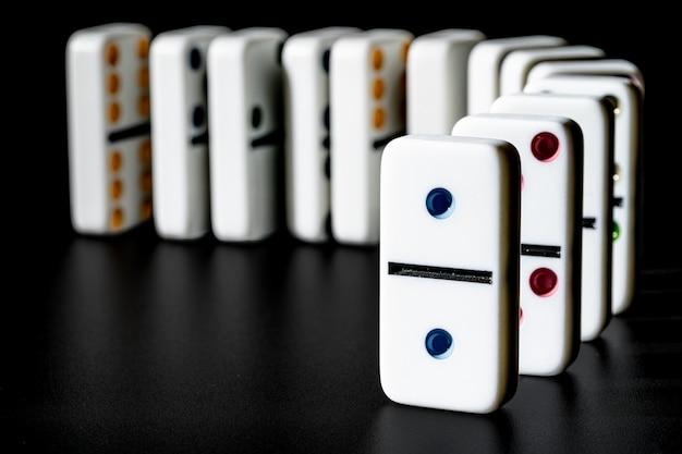 Domino che stanno in fila su fondo nero