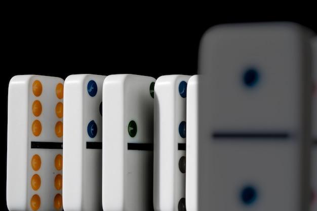 Domino in piedi in fila sulla superficie nera