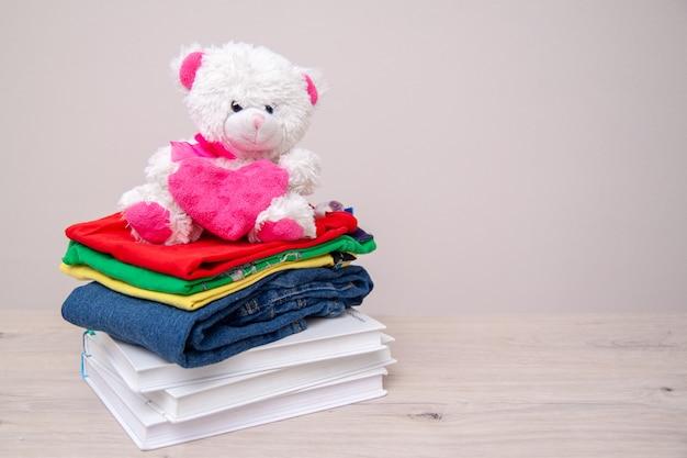 Dona merci con vestiti per bambini, libri, materiale scolastico e giocattoli.