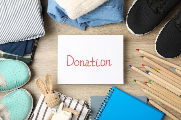 Donazione di testo, vestiti e accessori diversi su fondo di legno