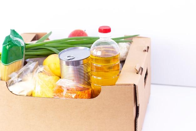 Donazione. scatola della spesa, aiutare i prodotti per chi è nel bisogno. scatola di donazione. scatola di cartone con generi alimentari su una superficie bianca.
