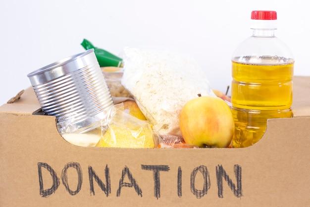 Donazione. scatola della spesa, aiutare i prodotti per chi ne ha bisogno. scatola di donazione. scatola di cartone con la donazione scritta con cibo su una superficie bianca.