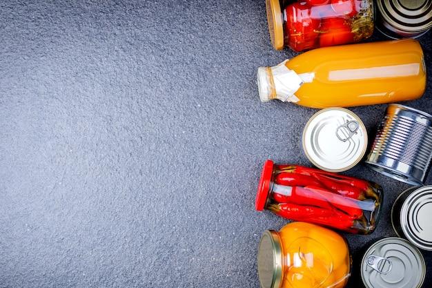 Donazioni di cibo su sfondo grigio, vista dall'alto con spazio di copia. varie conserve vegetali, carne, pesce e frutta in lattine e succo in bottiglia.