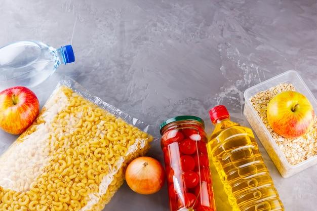 Donazioni di cibo su uno sfondo grigio. forniture alimentari. vista dall'alto