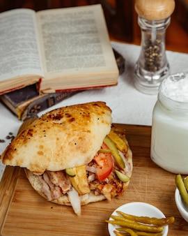 Doner di pollo nel pane con patatine fritte cetriolo pomodoro