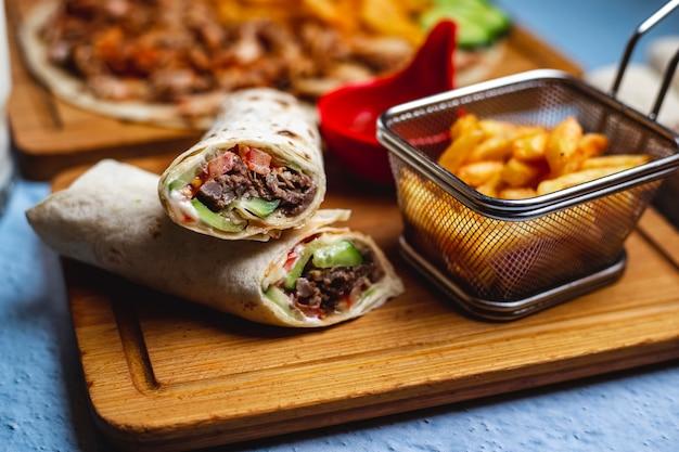 Doner di vista laterale con la salsa di pomodori e le patate fritte del cetriolo della carne su un bordo