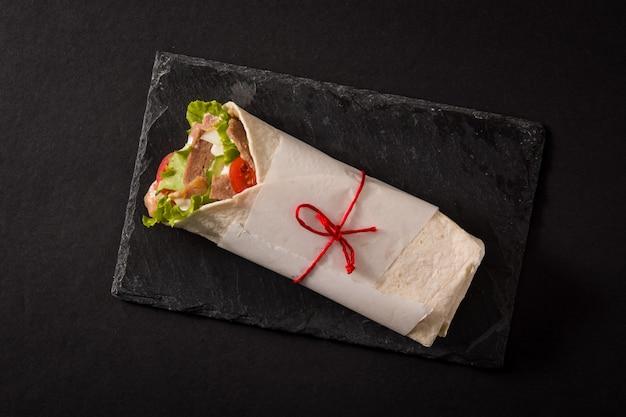Doner kebab o shawarma sandwich sulla superficie di ardesia nera vista dall'alto.