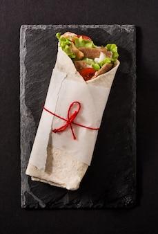 Doner kebab o shawarma sandwich sulla vista dall'alto di ardesia nera