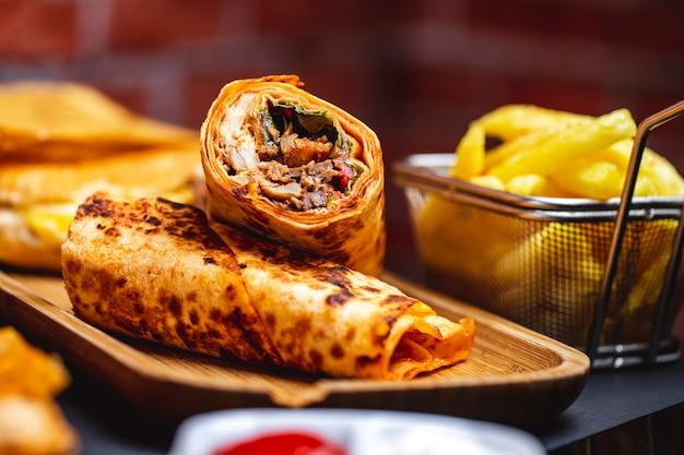 Doner vista laterale con pollo alla griglia verdi lattuga pomodoro e patatine fritte sul tavolo