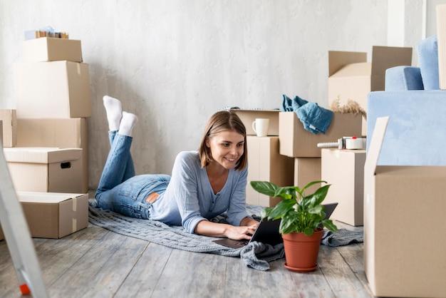 Donna a casa con scatole e pianta per uscire