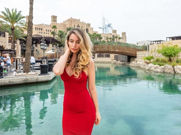 Donna a dubai, emirati arabi uniti. signora attraente che porta un vestito rosso. sentimenti solitari di umore triste