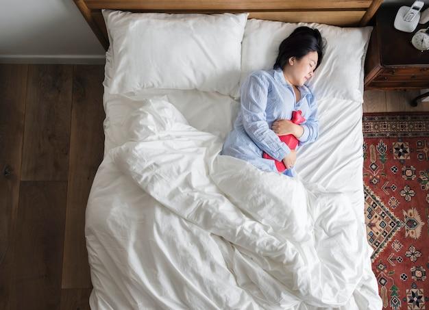 Donna a letto mettendo un impacco caldo sulla sua pancia