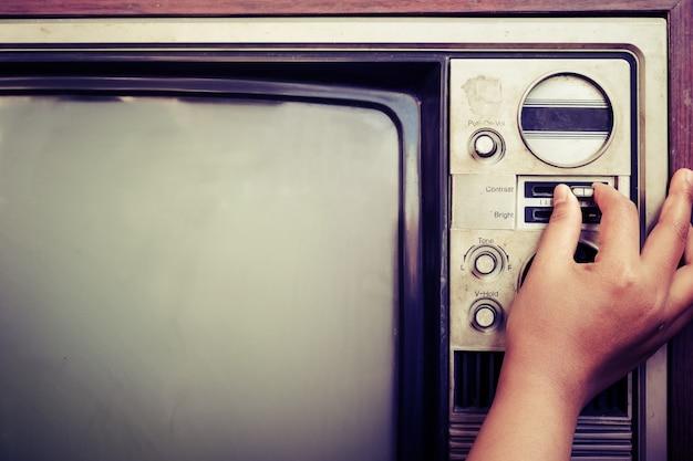 Donna a mano che sintonizza la televisione vintage con il pulsante di controllo. retro immagine elaborata.