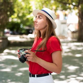 Donna a metà colpo con cappello e macchina fotografica